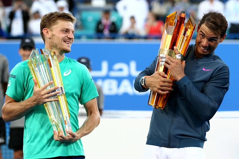 Spain's Rafael Nadal (R) poses with the winner's trophy with Belgium's David Goffin after the final of the Mubadala World Tennis Championship 2016 in Abu Dhabi on December 31, 2016. Nadal won 6-4, 7-6. (AFP Photo/Nezar Balout)