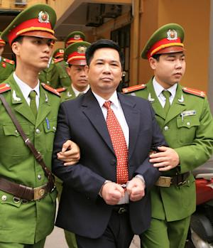 FILE - In this April 4, 2011, file photo dissident lawyer Cu Huy Ha Vu is escorted by police out of a courtroom after being convicted of spreading propaganda against the state and sentenced to seven years in prison and three years of house arrest at the one-day trial in Hanoi, Vietnam. Vu, the dissident son of one of Vietnam's founding revolutionaries, proclaimed his innocence during an appeals trial Tuesday Aug. 2, 2011, saying he's not against the Communist Party but supports a multiparty system. (AP Photo/Vietnam News Agency, Thong Nhat, File) NO SALES