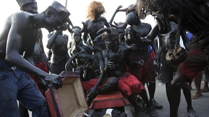 Revellers sit on a fake coffin containing a human skull as they take part in the Carnival 2016 parade in Port-au-Prince, Haiti