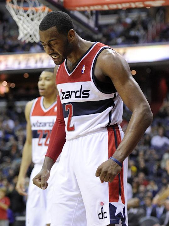 Washington Wizards guard John Wall (2) reacts during the second half of an NBA basketball game against the Milwaukee Bucks, Friday, Dec. 6, 2013, in Washington. The Bucks won 109-105 in overtime