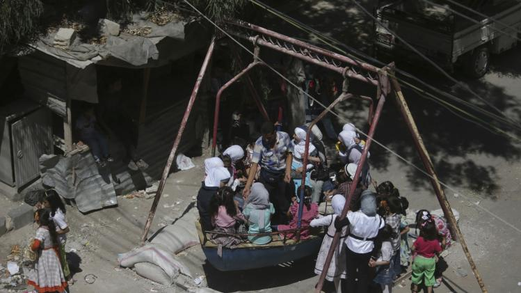 Children ride on a swing during Eid al-Fitr in the Duma neighbourhood of Damascus