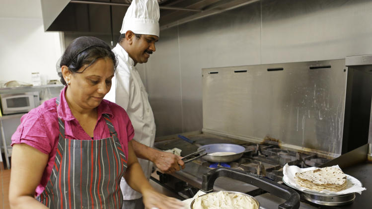 In this June 25, 2014 photo Anju Patel, left, and Charly Varghese, prepare Roti, an Indian bread, for the noon meal for residents at one of the two kitchens at ShantiNiketan, a retirement community for people from India, in Tavares, Fla. ShantiNiketan is one of a growing number of niche retirement communities aimed at people of specific ethnic backgrounds, hobbies or collegiate allegiances. (AP Photo/John Raoux)