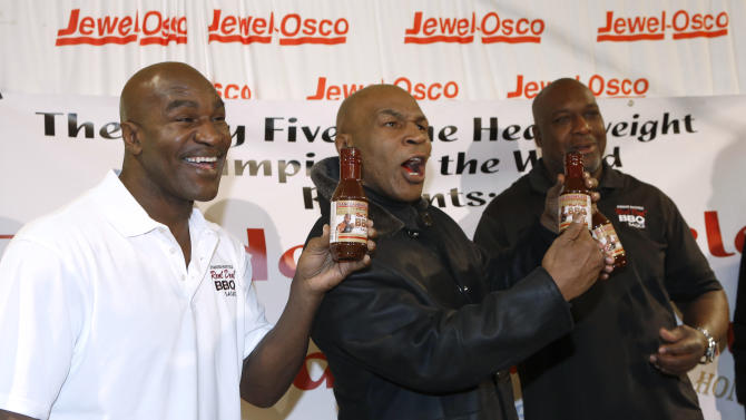 Former heavyweight champions Mike Tyson, center, and Evander Holyfield, left, pose with Henry Tillman, heavyweight gold medalist at the 1984 Los Angeles Olympics, during a promotional event for Holyfield's Real Deal barbecue sauce at a Chicago grocery store Saturday, Feb. 16, 2013. (AP Photo/Charlie Arbogast)