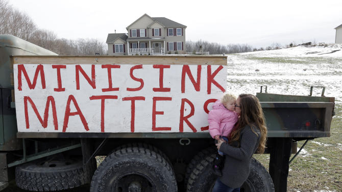 In this Thursday, Feb. 7, 2013 photo, Leanne Baum holds her daughter Hannah on a road outside their home in Minisink, N.Y. The construction site for a natural gas compressor station is across the road from the house. (AP Photo/Mike Groll)