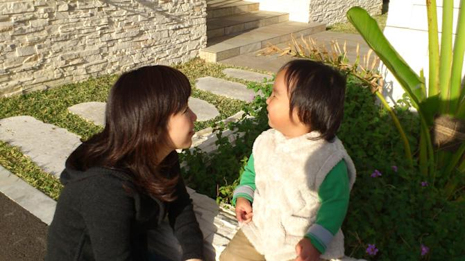 """In this photo released by Minako Kubota, Kubota chats with her two-year-old son in Naha, Okinawa, Japan. Okinawa is about as far away as one can get from Fukushima without leaving Japan, and that is why Kubota is here. Petrified of the radiation spewing from the Fukushima Dai-ichi nuclear plant that went into multiple meltdowns last year, Kubota grabbed her children, left her skeptical husband and moved to the small southwestern island. More than a thousand people from the disaster zone have done the same thing. """"I thought I would lose my mind,"""" Kubota told The Associated Press in a recent interview. """"I felt I would have no answer for my children if, after they grew up, they ever asked me, """"Mama, why didn't you leave?"""" (AP Photo/Courtesy of Minako Kubota)"""