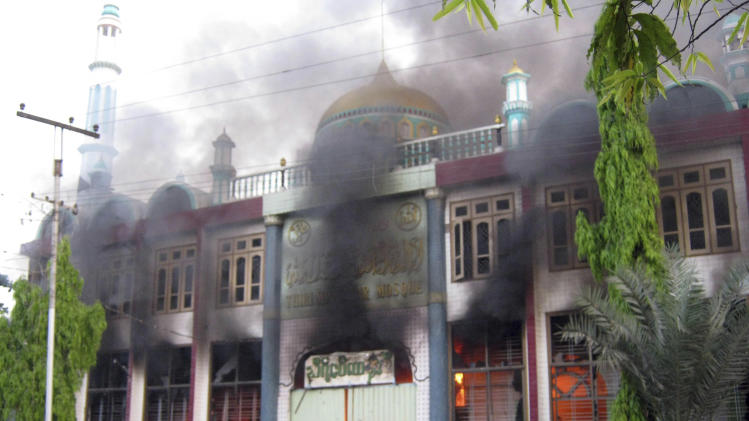 In this Thursday, March. 21, 2013 photo, smoke billows from a burning mosque following ethnic unrest between Buddhists and Muslims in Meikhtila, Mandalay division, about 550 kilometers (340 miles) north of Yangon, Myanmar. Burning fires from two days of Buddhist-Muslim violence that killed at least 20 people smoldered across a central Myanmar town Friday as residents cowered indoors amid growing fears the country's latest bout of sectarian bloodshed could spread. The government's struggle to contain the unrest in Meikhtila is proving another major challenge President Thein Sein's reformist administration as it attempts to chart a path to democracy after nearly half a century of military rule that once crushed all dissent. (AP Photo)
