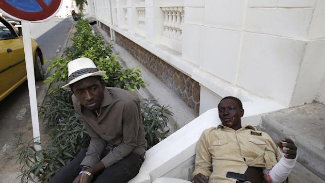 University student Mansour Niang, 27, right, who set himself on fire to protest grading changes that would keep him from continuing his studies, rests alongside friend Leon Mame Birame Faye, outside the entrance to the emergency ward, after being treated for burns on his arm and face at the main municipal hospital, in Dakar, Senegal Friday, March 15, 2013. Niang and two other students who tried to immolate themselves Friday are part of a group of 50 geography majors who say a new grading system has unfairly left them one credit short of receiving their diplomas, and will block them from continuing to their fourth-year masters degree at the public university. Student witnesses said students unconnected to the protest immediately threw sand on Niang to put out the fire and stopped the two other students from setting themselves alight. (AP Photo/Rebecca Blackwell)