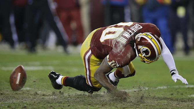 Washington Redskins quarterback Robert Griffin III falls after twisting his knee while reaching for a loose ball during the second half of an NFL wild card playoff football game against the Seattle Seahawks in Landover, Md., Sunday, Jan. 6, 2013. (AP Photo/Matt Slocum)