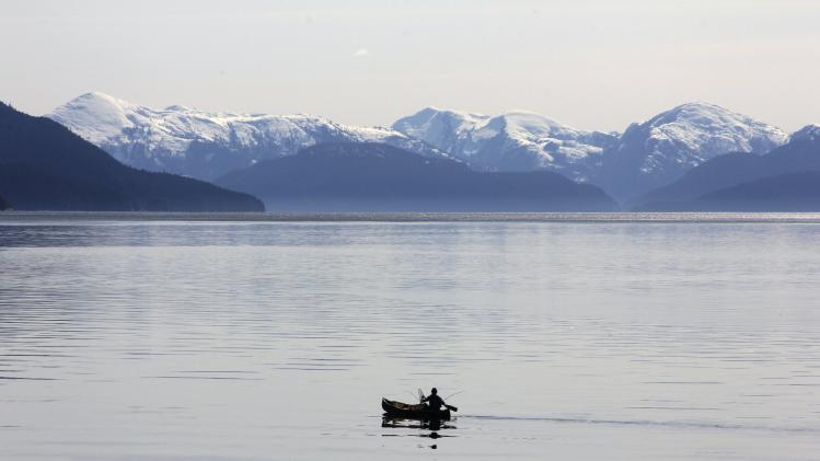 A fisherman paddles the waters of the Kitimat Arm on the Douglas Channel in his canoe in northern British Columbia