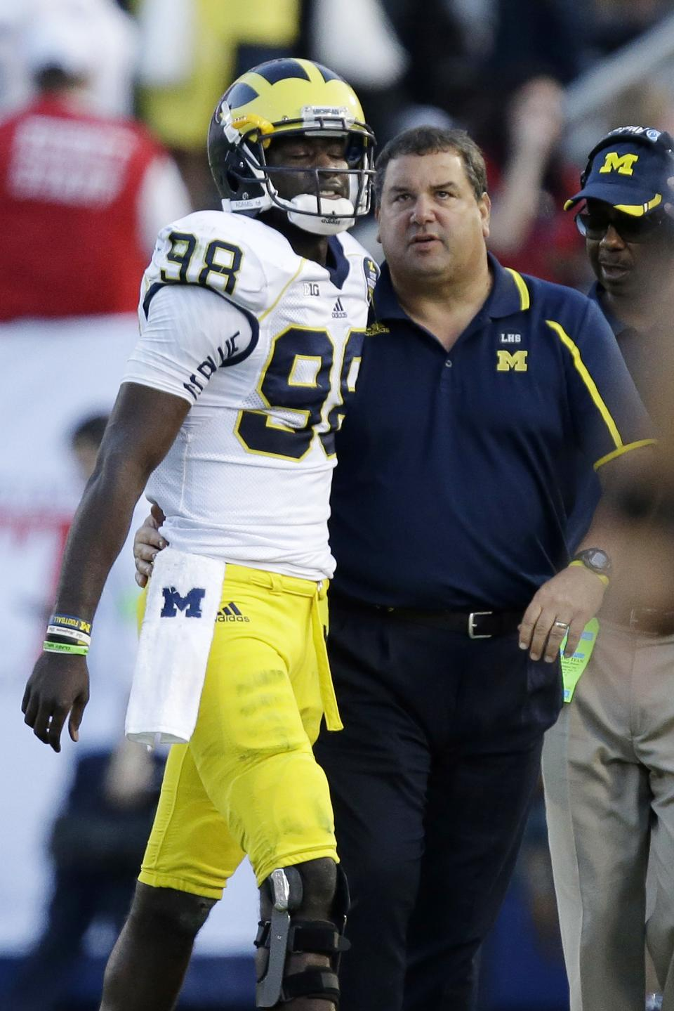Michigan head coach Brady Hoke, right, talks with Michigan quarterback Devin Gardner (98) during the second quarter an NCAA college football game against Penn State in State College, Pa., Saturday, Oct. 12, 2013. (AP Photo/Gene J. Puskar)
