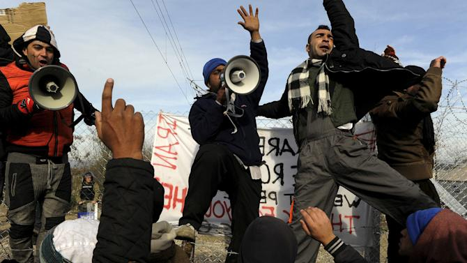 Stranded migrants shout slogans during a protest demanding to cross the Greek-Macedonian border, near the village of Idomeni
