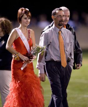 Whitney Kropp is escorted by her father, Jason Kropp onto the Ogemaw Heights High School football field Friday night, Sept. 28, 2012, in West Branch, Mich. Kropp was named to the homecoming court of the 800-student school earlier this month, but said she felt betrayed after some students suggested her selection was a joke. (AP Photo/Detroit News, John M. Galloway)  DETROIT FREE PRESS OUT; HUFFINGTON POST OUT