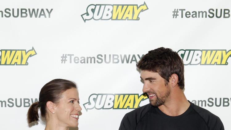 Whitney Phelps, left, is joined by her bother, Olympic swimming champion Michael Phelps, as as she announces that she will run the ING New York City Marathon with Team SUBWAY at the Chelsea Piers Sport Center, Monday, Oct. 15, 2012 in New York. (Photo by Jason DeCrow/Invision for SUBWAY/AP Images)
