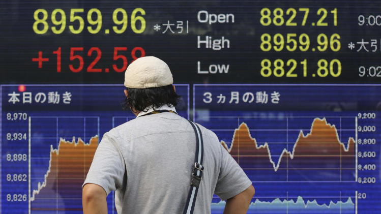 A man looks at an electronic stock indicator in Tokyo Wednesday, Sept. 12, 2012 as Japan's Nikkei 225 index rose 1.7 percent to close at 8,959.96. (AP Photo/Shizuo Kambayashi)