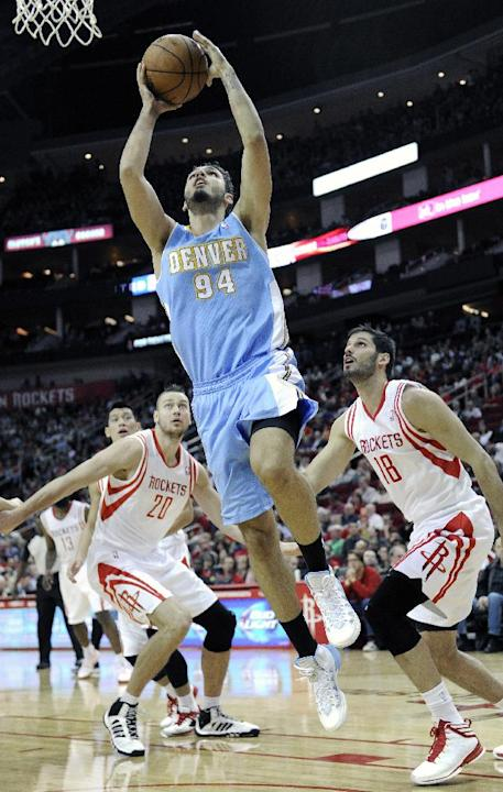Denver Nuggets' Evan Fournier (94) goes to the basket between Houston Rockets Donatas Motiejunas (20) and Omri Casspi (18) in the first half of an NBA basketball game Saturday, Nov. 16, 2013, in Houst