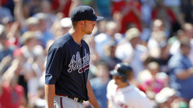 Atlanta Braves' Mike Minor, left, looks to the outfield as Boston Red Sox's Cody Ross rounds third base on a three-run home run in the fourth inning of a baseball game in Boston, Sunday, June 24, 2012. (AP Photo/Michael Dwyer)