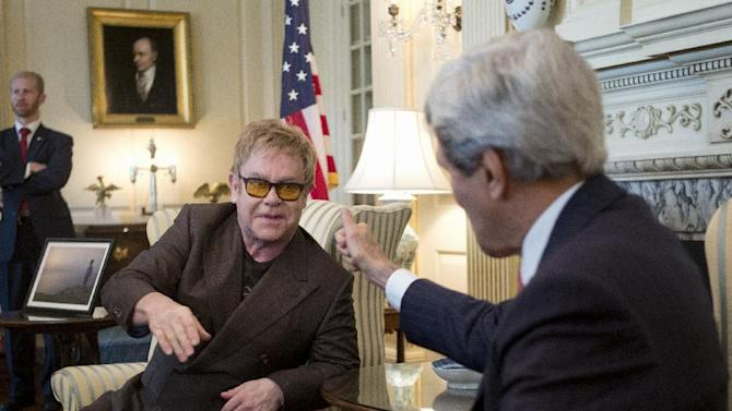 Secretary of State John Kerry gives the thumbs up to British musician Elton John as they talk to media at the State Department in Washington, Friday, Oct. 24, 2014, about the President's Emergency Plan for AIDS Relief (PEPFAR) and the work of the Elton John AIDS Foundation. (AP Photo/Carolyn Kaster)