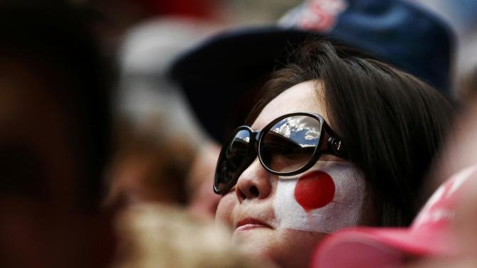 A supporter of Nishikori of Japan watches him play Wawrinka of Switzerland in their men's singles quarter-final match at the Australian Open 2015 tennis tournament in Melbourne