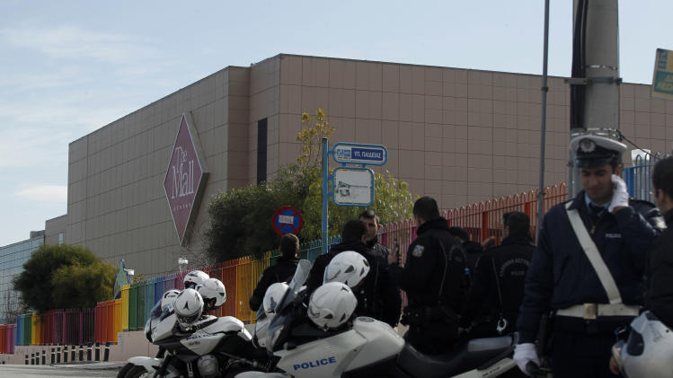 Police officers secure the street in front of a mall following a blast in Athens, Sunday, Jan. 20 2013. A bomb exploded Sunday at a shopping mall in Athens, slightly wounding two security guards, police said. (AP Photo/Kostas Tsironis)