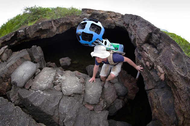 In this May 2013 photo provided by Google, Daniel Orellana of the Charles Darwin Foundation climbs out of an Isabela island where he was collecting imagery on the Galapagos. The lava landscapes found