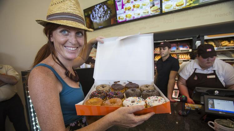 Patron Caila Ball-Dionne shows her purchase at a newly opened Dunkin' Donuts store in Santa Monica