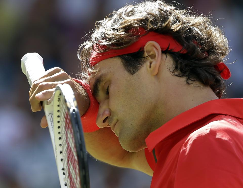 Roger Federer of Switzerland wipes his face as he competes with Andy Murray of Great Britain during the gold medal men's singles match at the All England Lawn Tennis Club in Wimbledon, London at the 2012 Summer Olympics, Sunday, Aug. 5, 2012. (AP Photo/Elise Amendola)