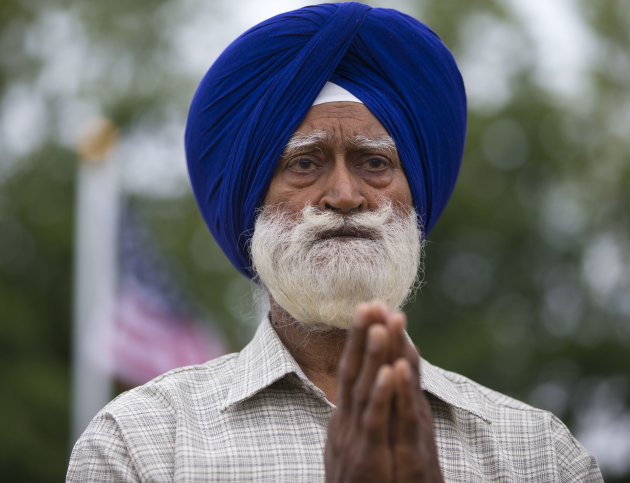 A man prays outside the Sikh Temple of Wisconsin in Oak Creek, Wis., Sunday, Aug. 12, 2012. More than 100 people gathered for the first Sunday prayer service since a white supremacist shot and killed