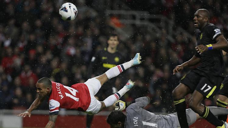 Arsenal's Theo Walcott, centre collides with Wigan Athletic's goalkeeper Joel Robles as he scores a goal against Wigan during their English Premier League soccer match at Arsenal's Emirates stadium in London, Tuesday, May  14, 2013. (AP Photo/Alastair Grant)