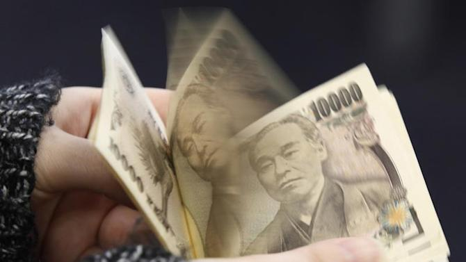 A woman counts Japanese 10,000 yen notes in Tokyo, in this picture illustration