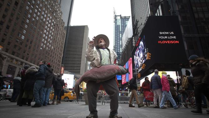 A man sings and dances with a giant fish in Times Square in the Manhattan borough of New York