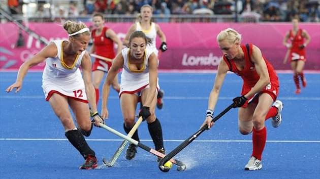 Belgium's Valcke and Vandermeiren challenge Britain's Danson during their women's Group A hockey match at the London 2012 Olympic Games at the Riverbank Arena on the Olympic Park