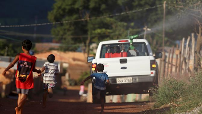 Children run as a municipal pick-up truck sprays a street with insecticide to kill the Aedes mosquito in Brasilia
