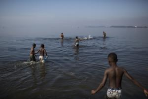 In this May 15, 2014 photo, kids play in the polluted …