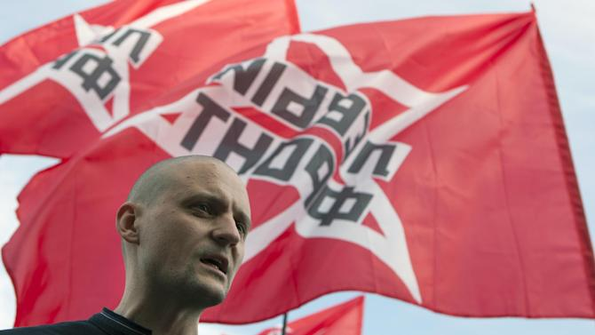 Left Front leader Sergei Udaltsov, with his movement flags in the background,  speaks at an opposition rally in support of opposition activists they allege were arrested over their role in a violent protest in May, in Moscow, Thursday, July 26, 2012. Opposition activists and rights groups called the arrests a part of a widening government crackdown on dissent that followed Vladimir Putin's election to a third presidential term in March. (AP Photo/Alexander Zemlianichenko)