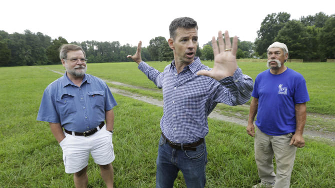 Martin Gallivan, College of William professor, center, gestures as Pamunkey Indian Jeff Brown, right, and  Randolph Turner, retired state archaeologist, left, listen during a tour of a farm field overlooking the York River in  Gloucester, Va., Monday, June 17, 2013. The field is known to many in Virginia as the place where Pocahontas interceded to rescue Capt. John Smith from her powerful father, Powhatan, who ruled a vast empire in 1607  in (AP Photo/Steve Helber)
