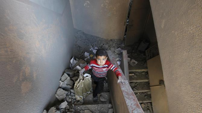 A Palestinian boy walks up the stairs of a house destroyed on Sunday by an Israeli strike in Gaza City, Monday, Nov. 19, 2012. The Palestinian civilian death toll mounted Monday as Israeli aircraft struck densely populated areas in the Gaza Strip in its campaign to quell militant rocket fire menacing nearly half of Israel's population. (AP Photo/Hatem Moussa)