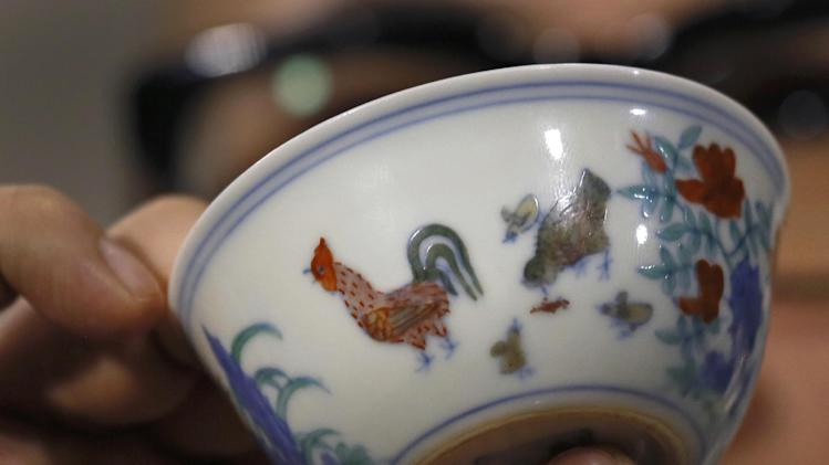 "The Meiyintang ""Chicken Cup"" from the Chinese Ming Dynasty (1368-1644) is displayed during a press conference in Hong Kong, Tuesday, April 8, 2014. Sotheby's said Shanghai collector Liu Yiqian won the bidding for the ""Chicken Cup,"" which is decorated with a rooster, hen and their chicks. Including the auction house's commission, the price for the small cup comes to HK$281.2 million (US$36.1 million), which Sotheby's said is a world record price for Chinese porcelain. (AP Photo/Vincent Yu)"