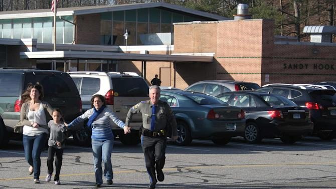 FILE - In this Friday, Dec. 14, 2012 file photo provided by the Newtown Bee, a police officer leads two women and a child from Sandy Hook Elementary School in Newtown, Conn., where a gunman opened fire. Contractors demolishing Sandy Hook Elementary School are being required to sign confidentiality agreements forbidding public discussion of the site, photographs or disclosure of any information about the building where 26 people were fatally shot last December. (AP Photo/Newtown Bee, Shannon Hicks, File) MANDATORY CREDIT: NEWTOWN BEE, SHANNON HICKS