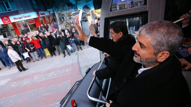 Senior Hamas leader Khaled Mashal and Turkish Prime Minister Ahmet Davutoglu greet people as they tour the central Anatolian city of Konya