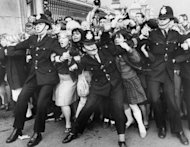 In this file picture from 1965, Beatles fans try to break through a police line at Buckingham Palace in London where the group were due to receive the Member of the British Empire (MBE) decoration from the Queen. The Beatles' debut tune that launched Britain into the '60s and helped to ignite a worldwide obsession for the four-man British rock band celebrates its 50th anniversary on Friday