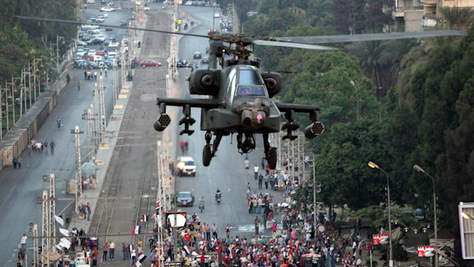 """A military attack helicopter flies near the presidential palace in Cairo, Egypt, Friday, July 5, 2013. The top leader of Egypt's Muslim Brotherhood has vowed to restore ousted President Mohammed Morsi to office, saying Egyptians will not accept """"military rule"""" for another day. General Guide Mohammed Badie, a revered figure among the Brotherhood's followers, spoke Friday before a crowd of tens of thousands of Morsi supporters in Cairo. A military helicopter circled low overhead. (AP Photo/Khalil Hamra)"""