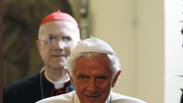 Pope Benedict XVI arrives, followed by Vatican secretary of state cardinal Tarcisio Bertone, to meet Milan's authorities and entrepreneurs at the archbishopric in Milan, Italy, Saturday, June 2, 2012. The pope in in Milan for the seventh World Encounter of Families, a welcome pastoral respite from an embarrassing and damaging leaks scandal at the Vatican that has engulfed the pontiff's personal butler. (AP Photo/Luca Bruno,Pool)