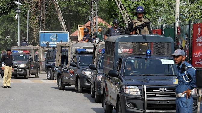 Pakistani police commandos stand alert as a bus carrying the Zimbabwe cricket team players arrives at the Gaddafi Stadium,  Saturday, May 23, 2015 for a practice session in Lahore, Pakistan. Zimbabwe will take on Pakistan in the second Twenty20 match on Sunday. (AP Photo/K.M. Chaudary)