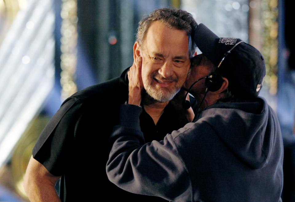 Actor Tom Hanks is kissed by David Wader, a stage manager for the 84th Academy Awards, Saturday, Feb 25, 2012 in Los Angeles, during rehearsals for Sunday's show. (AP Photo/Chris Carlson)
