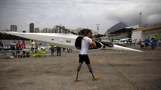 A paracanoe athlete carries his kayak after a practice for the Aquece Rio Canoe Sprint competitions at Rodrigo de Freitas lagoon in Rio de Janeiro