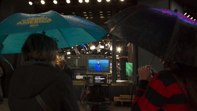 Spectators watch a live broadcast of a weatherman outside the Good Morning America studios in Times Square, Monday, Oct. 29, 2012, in New York. Hurricane Sandy continued on its path Monday, forcing the shutdown of mass transit, schools and financial markets, sending coastal residents fleeing, and threatening a dangerous mix of high winds and soaking rain. (AP Photo/ John Minchillo)