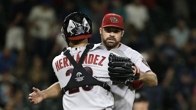 Arizona Diamondbacks closing pitcher Josh Collmenter, right, embraces catcher Oscar Hernandez after the team defeated the Seattle Mariners 8-4 in a baseball game, Tuesday, July 28, 2015, in Seattle.  (AP Photo/Elaine Thompson)