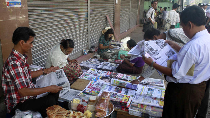 People read weekly journals to buy at a roadside shop in Yangon, Myanmar, Tuesday, Feb. 28, 2012. Newspaper articles that would have been rejected by Myanmar's draconian state censors just months ago are making it into print, in one of many signs that the long-repressed country is becoming more open. Though censorship persists, especially on political issues, the government is allowing many stories to be published without prior review, and journalists who were once jailed, beaten or blacklisted are testing the new boundaries. (AP Photo/Khin Maung Win)