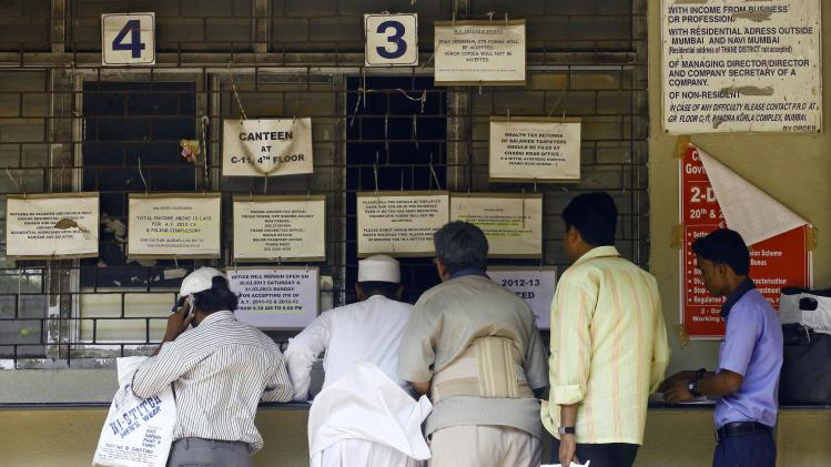 In this Tuesday, March 26, 2013 photo, Indians stand in a queue to file tax papers at an Income Tax office in Mumbai, India. In a country of 1.2 billion people, a country where years of staggering economic growth have created tens of thousands of new millionaires annually and a recent slowdown has done little damage to a thriving luxury goods market, far less than .01 percent of the population admits they are in the top tax bracket. Less than 3 percent of Indians file income tax returns at all, and officials say only about 1.5 million taxpayers declare earning more than 1,000,000 rupees per year (about $18,000). (AP Photo/Rafiq Maqbool)