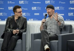 """Bono listens to The Edge at a presser for """"From The Sky Down"""" in Toronto. (Darren Calabrese, AP/The Canadian Press)"""